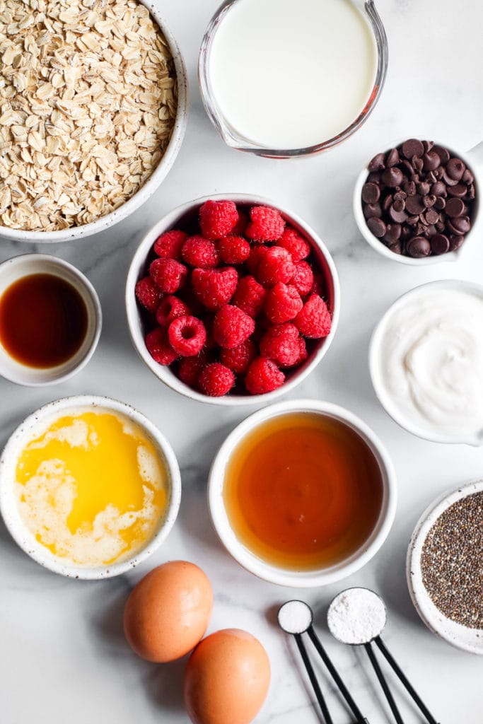 All ingredients for raspberry baked oatmeal in small bowls on a marble counter