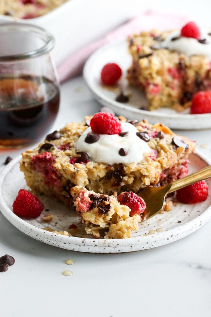 A piece of raspberry baked oatmeal on a speckled plate topped with whipped cream