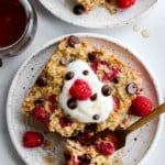 Raspberry baked oatmeal with chocolate chips on a speckled plate with a gold fork and topped with whipped cream
