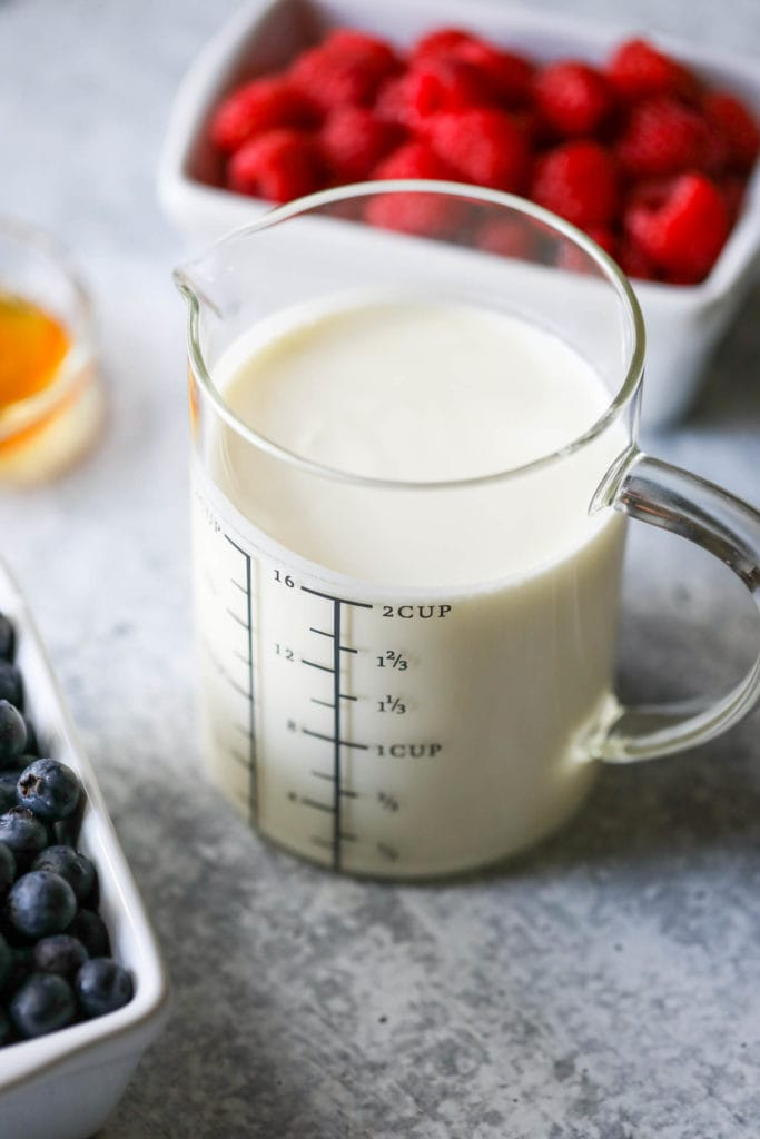 A measuring up filled with creamy kefir as part of the ingredients for creamy berry popsicles