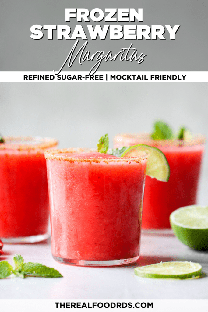 Straight on shot of frozen strawberry margaritas with coconut sugar on the rim and limes and mint as garnish