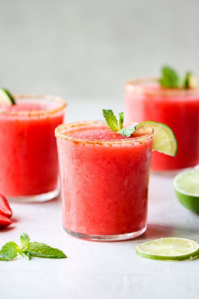 A coral colored frozen strawberry margarita in a glass with coconut sugar on the rim and a lime slice on the side