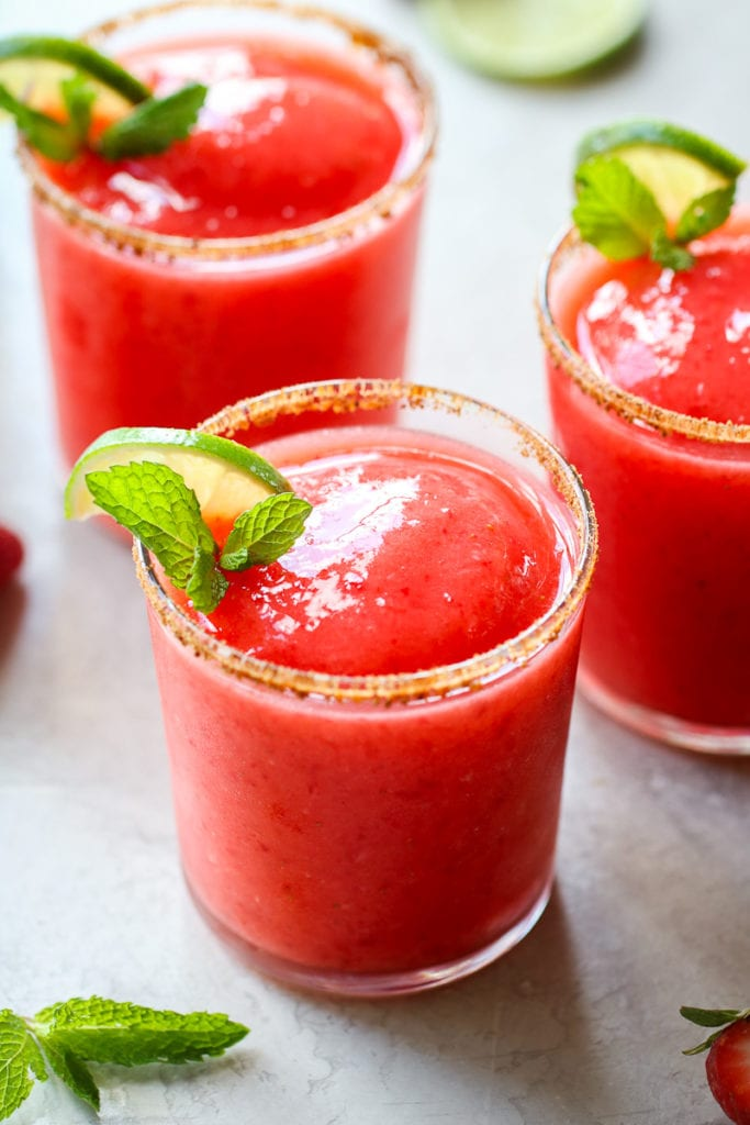 Three strawberry margaritas freshly blended in short glasses with limes and mint as garnish