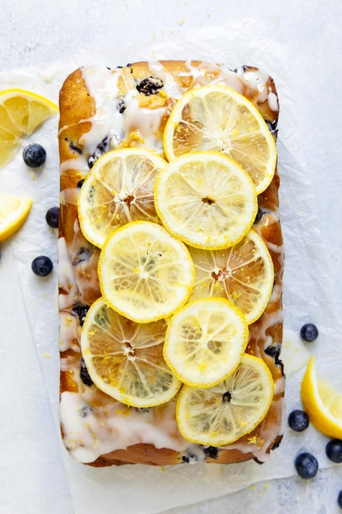 An overhead view of a lemon blueberry loaf topped with lemon glaze and thin lemon slices