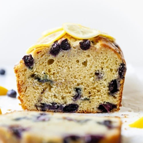 Freshly cut lemon blueberry loaf topped with thin lemon slices.