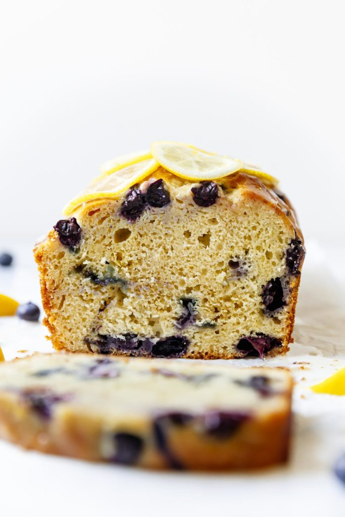 Lemon Blueberry Bread with a slice freshly cut from the loaf to show juicy blueberries and gluten-free texture.