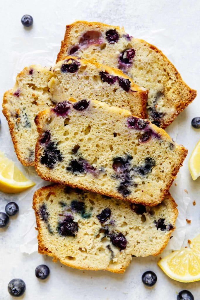 Four thick slices of lemon blueberry bread freshly cut and stacked against each other.