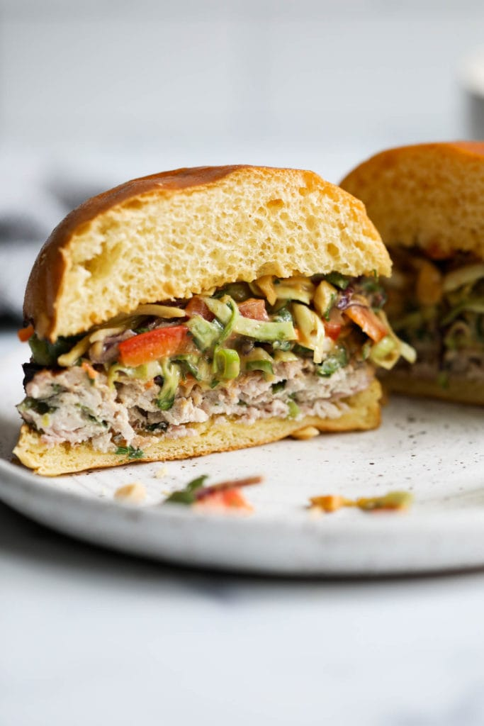 A grilled pork burger in a gluten-free bun and topped with creamy Thai slaw cut in half