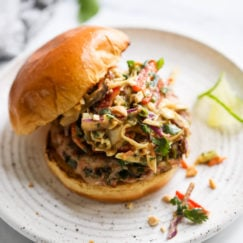 A grilled pork burger topped with creamy Thai Slaw in a gluten-free bun