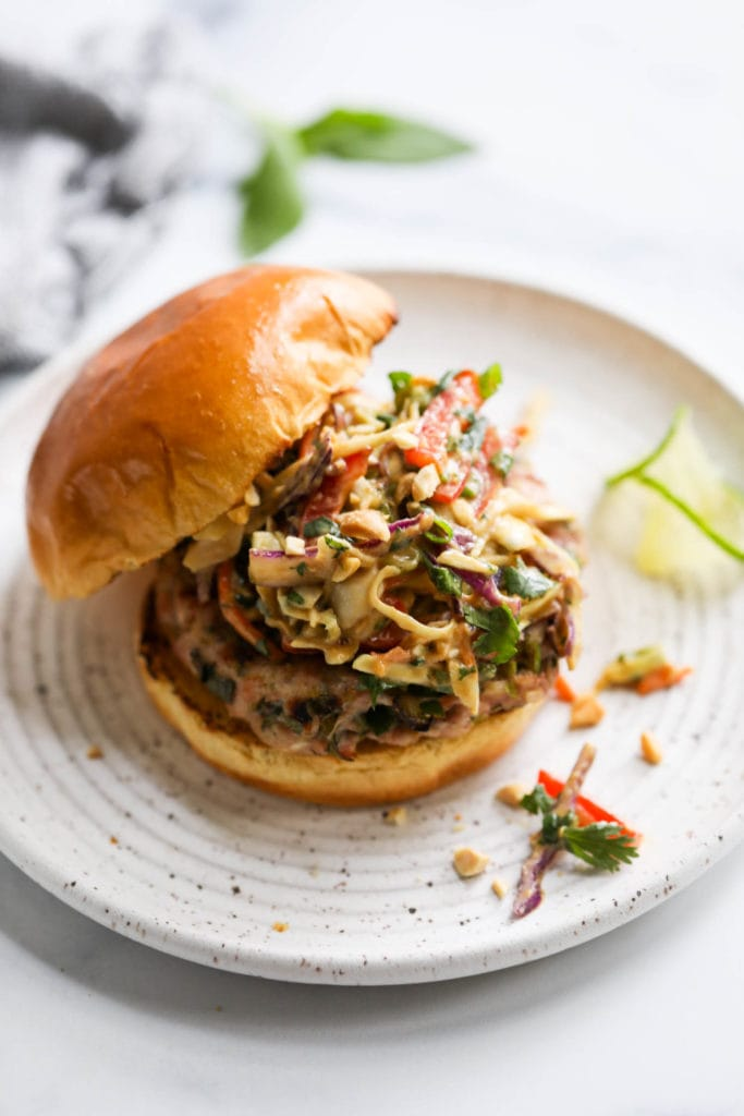 A grilled pork burger topped with creamy Thai slaw on a toasted gluten-free bun