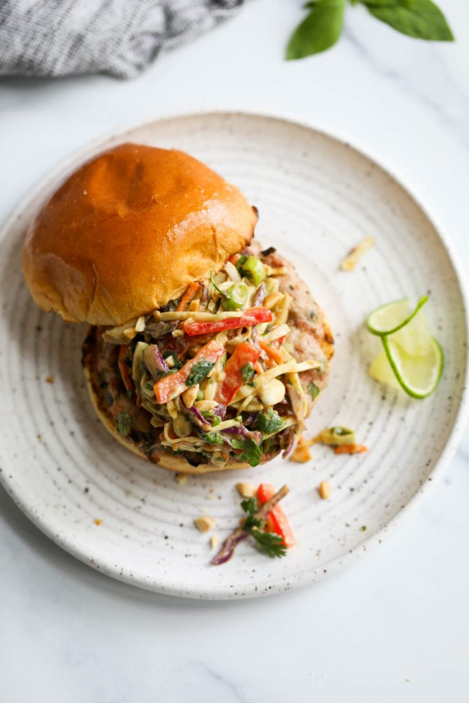A grilled pork burger topped with creamy Thai-inspired slaw on a gluten-free toasted bun