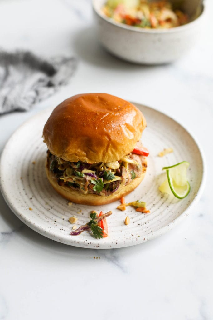 A grilled pork burger topped with creamy Thai slaw in a gluten-free toasted bun