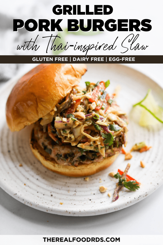 A grilled pork burger topped with creamy Thai slaw on a toasted bun