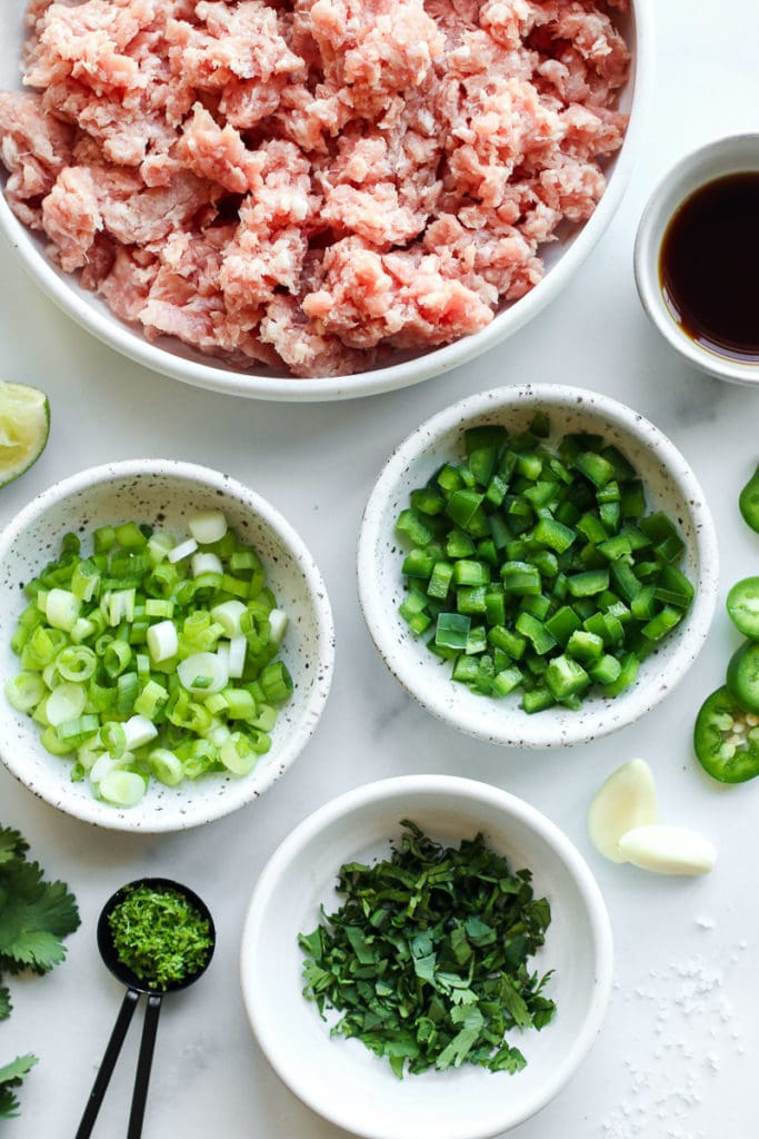 Ingredients for pork burgers including green onions, green peppers, jalapenos, and fresh herbs in small bowls.