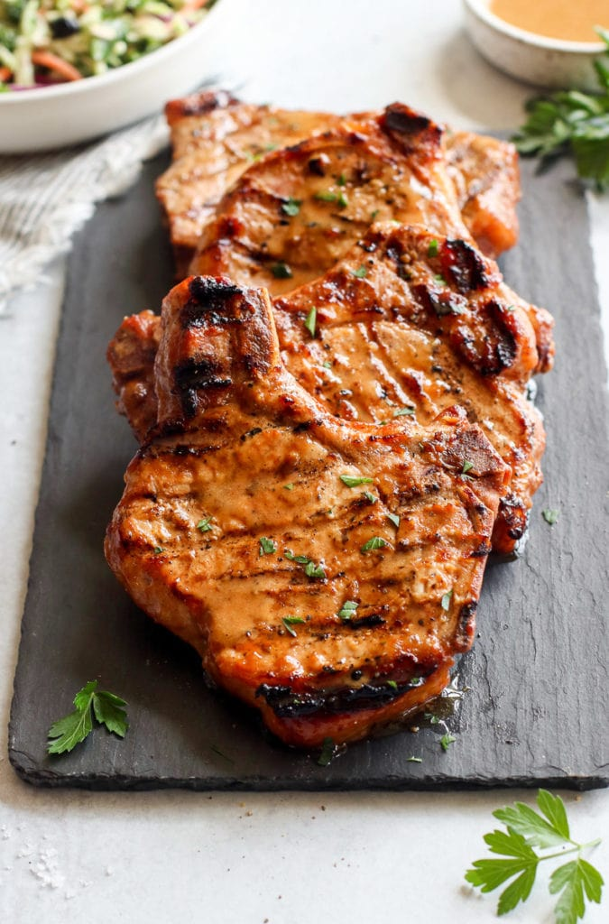 Four marinated grilled pork chops with a homemade honey mustard dressing resting on a black slate board