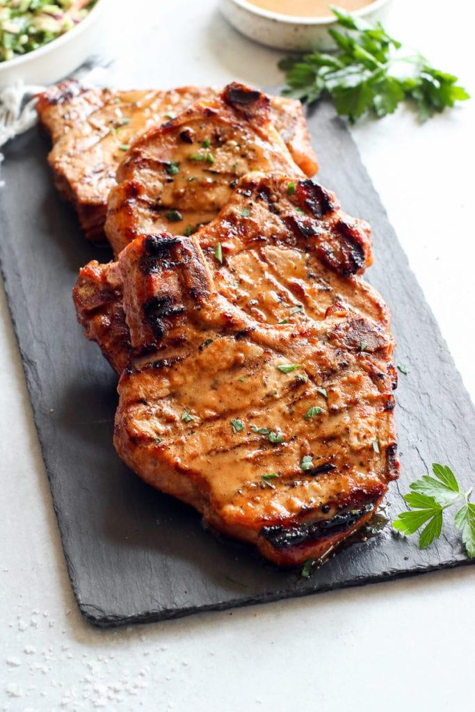 Four juicy bone-in pork chops freshly grilled resting on a black slate cutting board glistening in honey mustard marinade