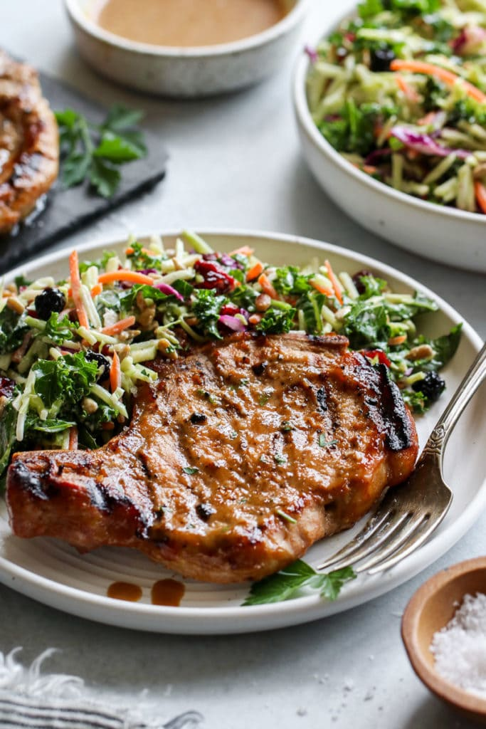 A marinaded grilled bone-in pork chop with grill marks on a white plate with a coleslaw salad on the side.