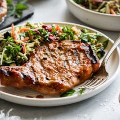 A juicy grilled pork chop marinated in homemade honey mustard marinade plated next to a side of coleslaw