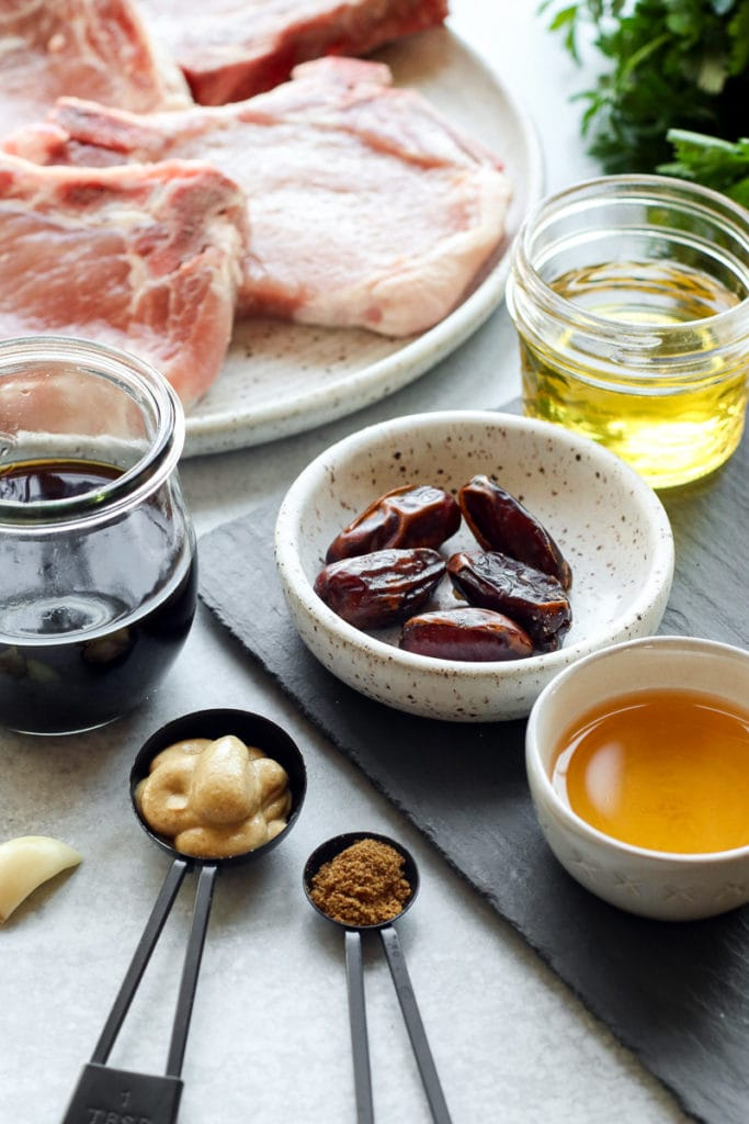 All ingredients for the pork chop marinade in measuring spoons, bowls, and small jars.