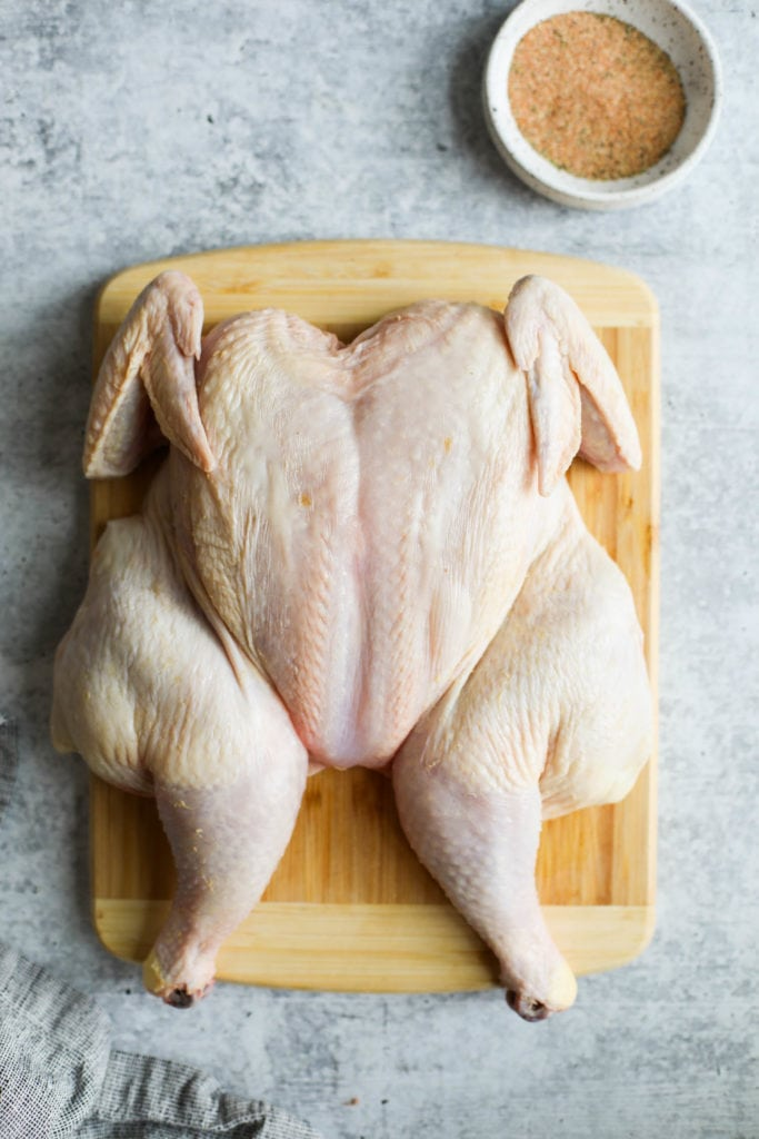 A raw whole chicken on a wooden cutting board