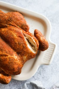A smoked spatchcock chicken with paprika rub served on a white platter with a deep cut in the breast so show tender meat.