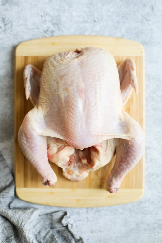 A raw whole chicken placed breast-side up on a wooden cutting board