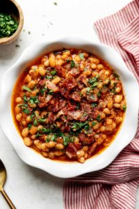A white scalloped bowl filled with Instant Pot Baked Beans and topped with bacon and herbs.