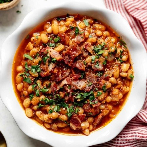 Instant Pot Baked Beans with bacon served in a white bowl with a red striped dish cloth next to the bowl