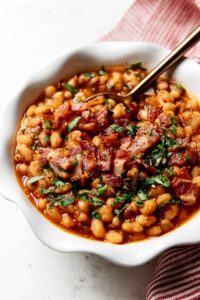 Instant Pot Baked Beans with bacon served in a white scalloped edge bowl with a gold spoon in the beans.