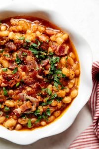 A bowl filled with Instant pot baked beans and topped with bacon crumbles and fresh herbs