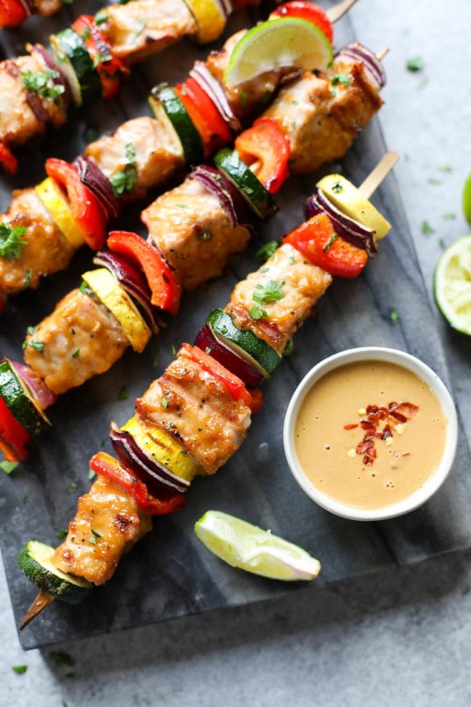 Pork kebabs with veggies on skewers served on a black platter with peanut sauce on the side