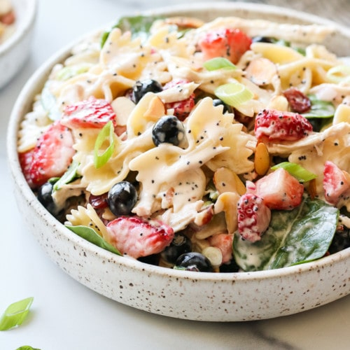 Creamy bow-tie noodle pasta mixed with shredded chicken, fresh berries, baby spinach, and creamy lemon poppy seed dressing in a low profile bowl