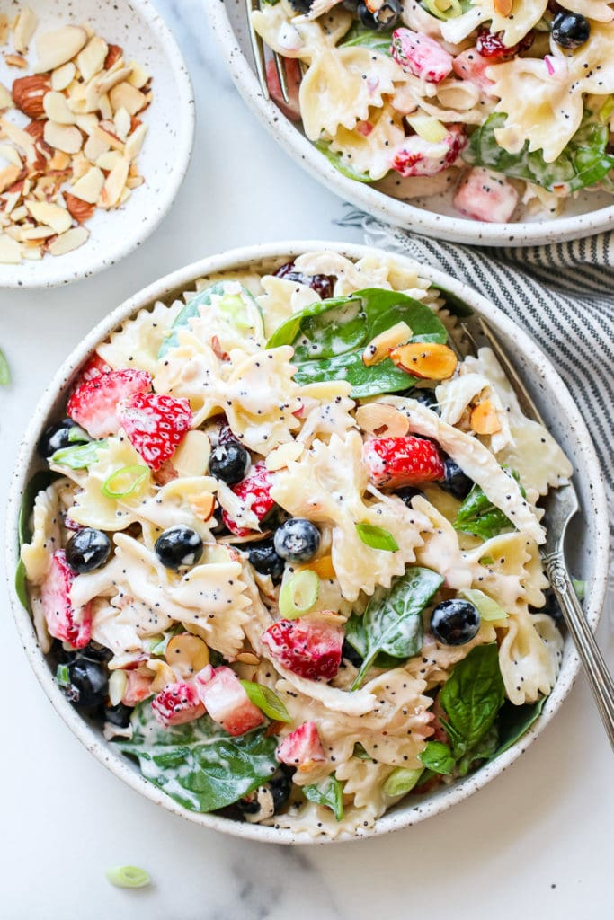Summer Pasta Salad with Chicken and Berries in a speckled, white, shallow, stoneware bowl.