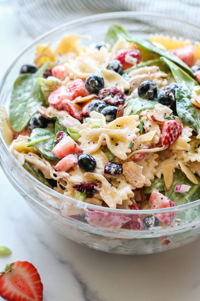 Summer Pasta Salad in a large, glass bowl, all tossed and ready to be served.