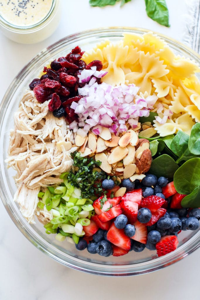 Ingredient for Summer Pasta Salad with Chicken and Berries in a large, glass mixing bowl.