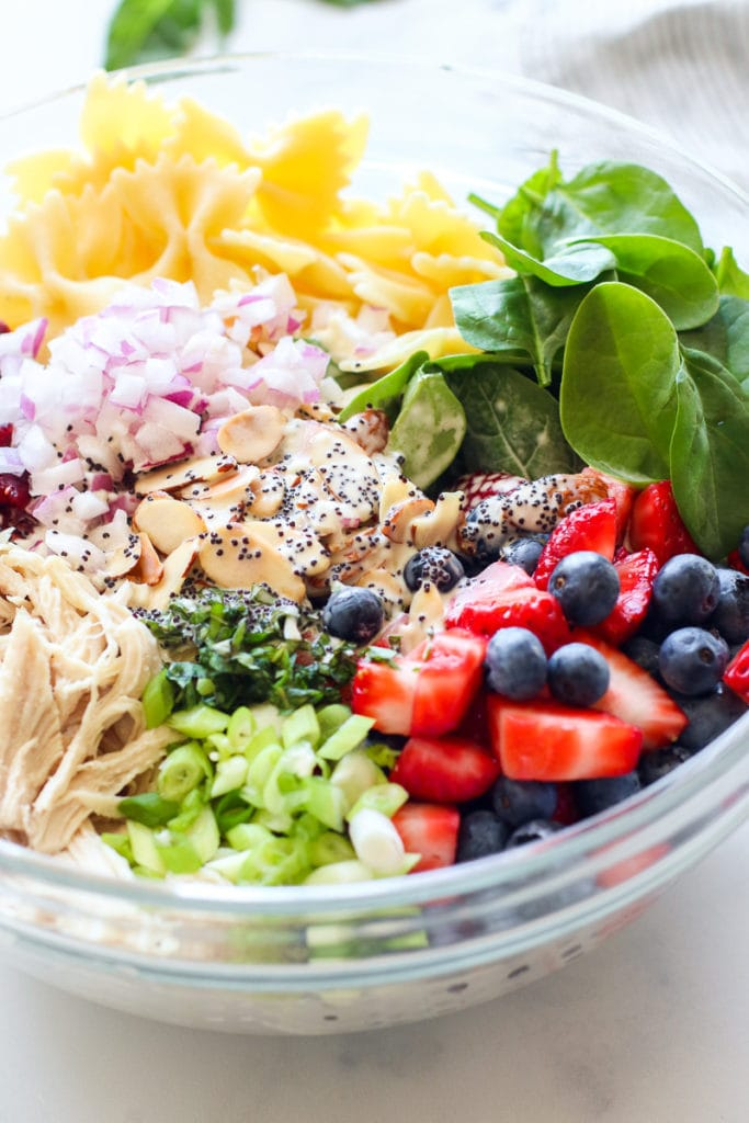 All of the ingredients for the Summer Pasta Salad in a large, clear mixing bowl.