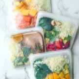 Four smoothie bags filled with fresh produce for healthy make-ahead smoothie bags