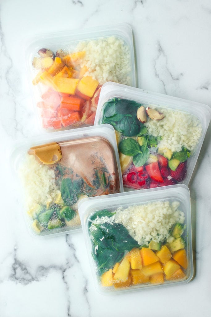 Four reusable freezer bags filled with healthy smoothie ingredients for DIY smoothie packs at home.