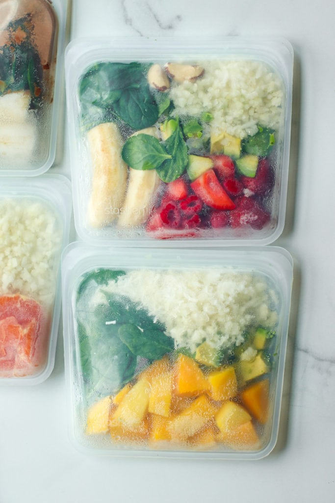 Close up of two frozen smoothie bags filled with fresh produce.