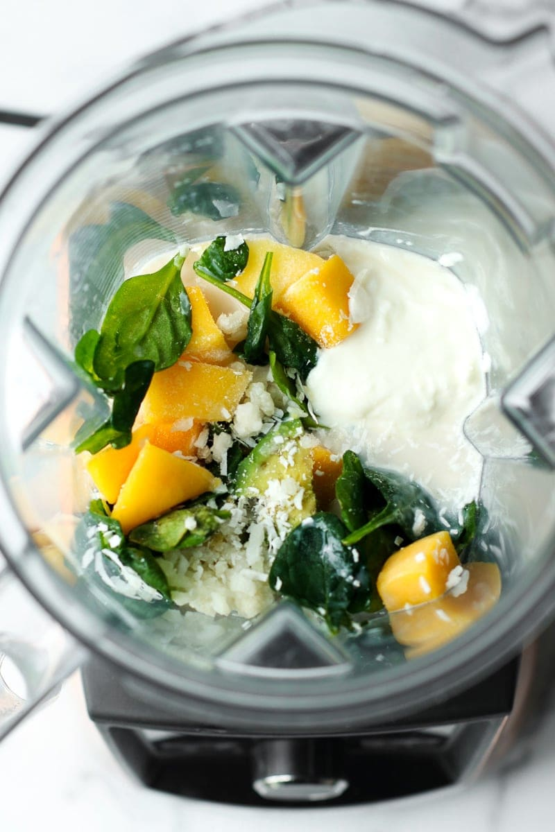 All ingredients for mango avocado energy smoothie in a blender cup