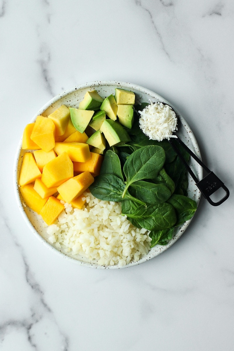 All ingredients for mango avocado energy smoothie bags on a plate