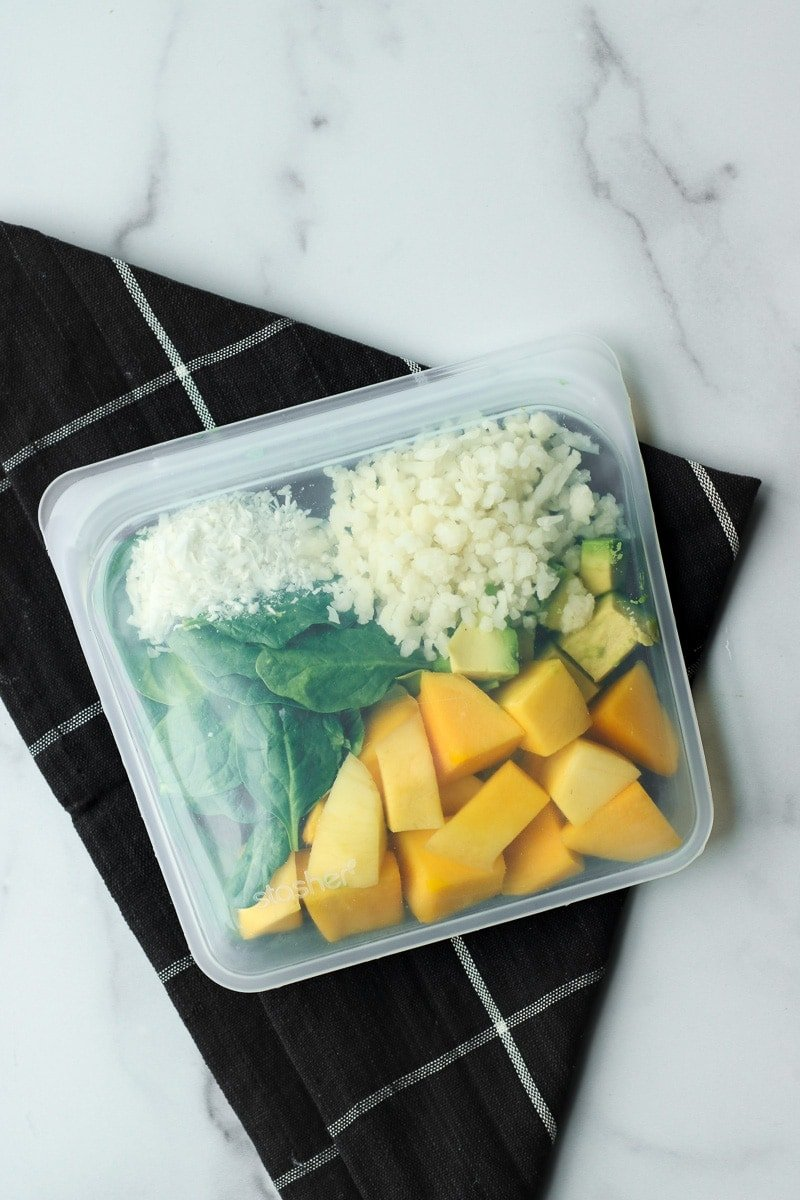 All ingredients for mango avocado smoothie in a reusable freezer bag