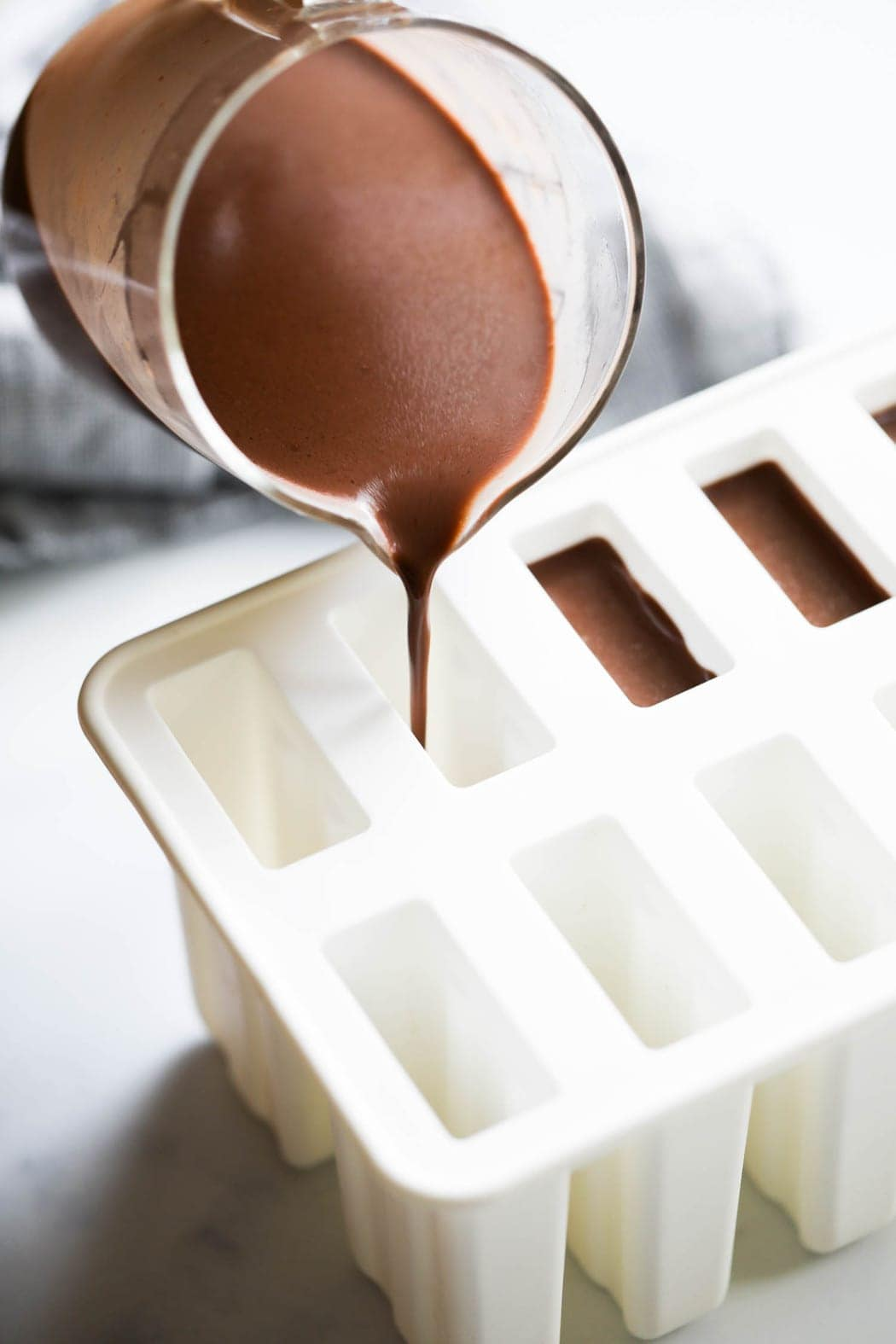 Creamy fudgesicle mixture being poured into popsicle molds