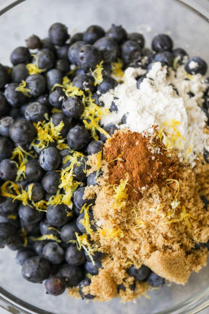 Fresh blueberries, brown sugar, cinnamon, and lemon zest in a mixing bowl
