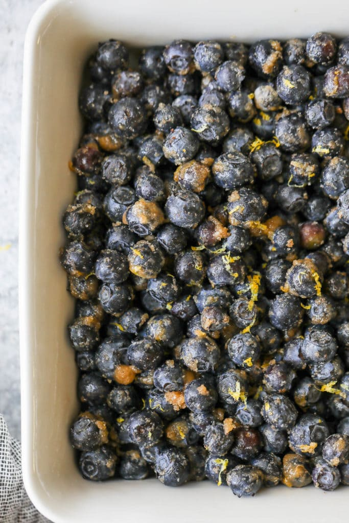Fresh blueberries tossed in brown sugar, cinnamon, and lemon zest spread evenly in a white baking dish