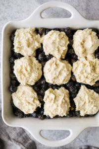 Gluten-free biscuit dollops on top of fresh blueberries in a white baking dish