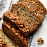 Thick slices of freshly baked zucchini bread topped with walnuts on a metal cooling rack