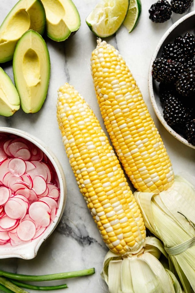Two freshly shucked corn on the cobs surrounded with a bowl of sliced radishes, a plate of blackberries, and thick slices of avocados.