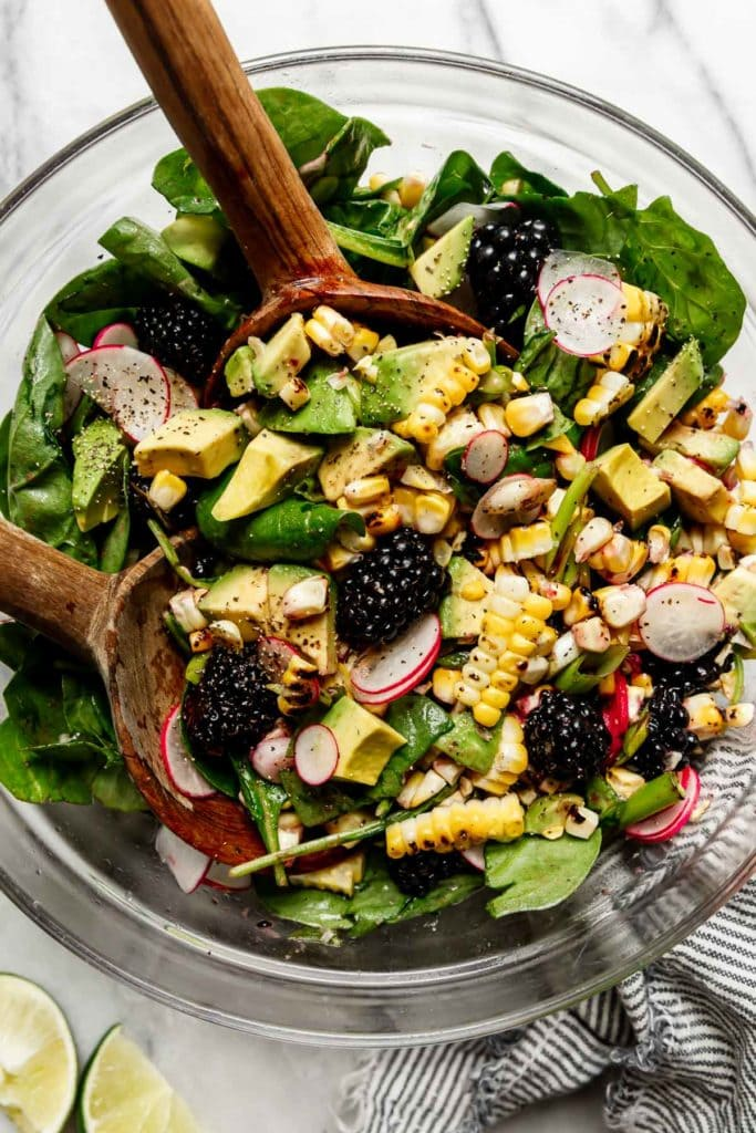 Grilled corn salad being tossed with wooden spoons to mix together blackberries, avocado, radishes, and spinach.