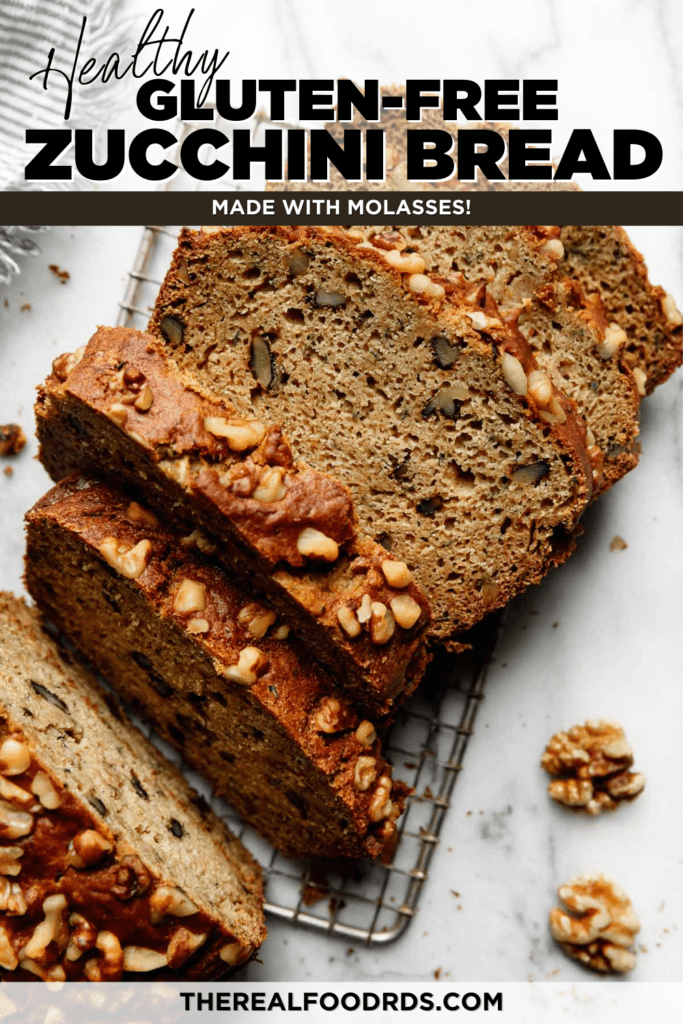 Thick slices of zucchini bread topped with walnuts on a metal cooling rack